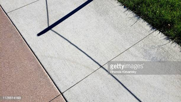 abstract shadows on city sidewalk - rhonda klevansky ストックフォトと画像