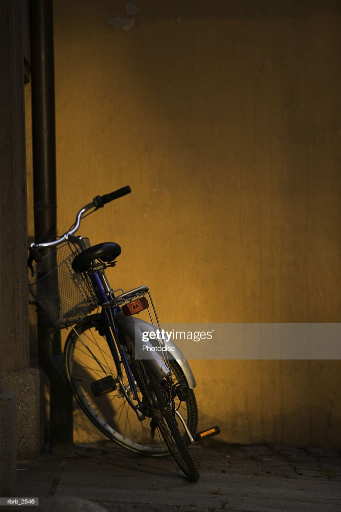 abstract shot of a lone bicycle as it leans against a wall : Foto de stock
