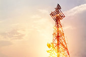 Abstract telecommunication tower Antenna and satellite dish at sunset sky background