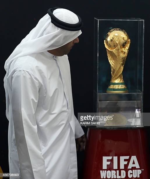 Abu Dhabi Airport chairman Ali alMansuri poses next to the FIFA World Cup 2014 trophy following its arrival in the Gulf emirate on December 15 2013...