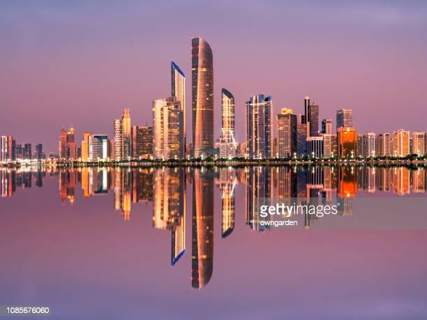 abu dhabi city skyline at twilight, united arab emirates - アブダビ ストックフォトと画像
