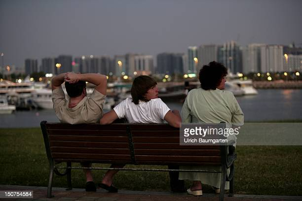Abu Dhabi Park bench with people in front of the skyline of Abu Dhabi
