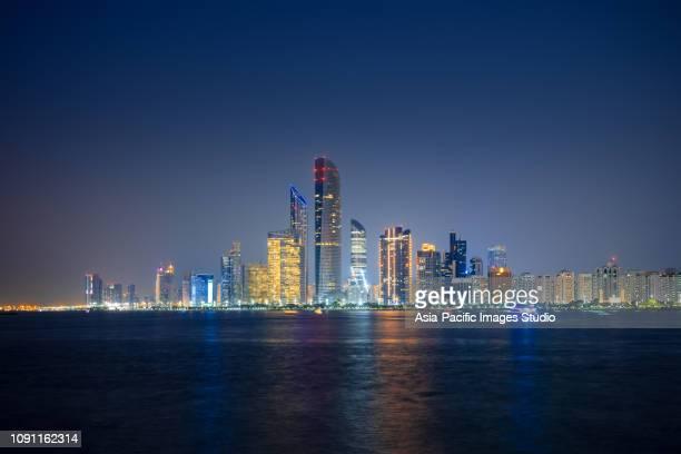 abu dhabi skyline at night - abu dhabi stock pictures, royalty-free photos & images