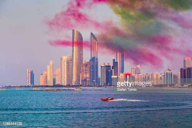 abu dhabi skyline covered with colorful air show smoke for the uae national day celebration - national holiday stock pictures, royalty-free photos & images