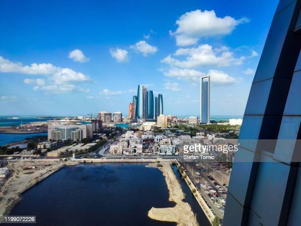 abu dhabi skyline view of the downtown buildings rising over the water - gulf countries stock pictures, royalty-free photos & images