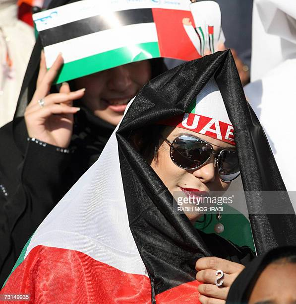 A supporter of the Emirati football team raps the national flag around her head ahead of the final Gulf Cup match between UAE and Oman in the Gulf...
