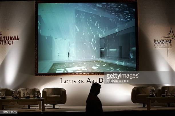 An Emirati sheikh passes in front of a picture of the future Louvre Abu Dhabi museum after a signing ceremony for a controversial agreement to build...
