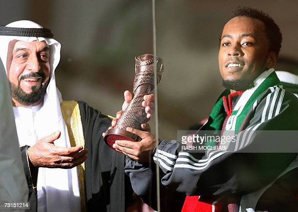 Emirati player Ismail Matar receives the trophy of Best Forward from UAE president Sheikh Khalifa Bin Zayed alNahayan after UAE's victory against...
