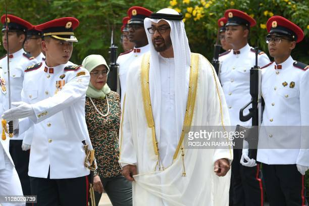 Abu Dhabi's Crown Prince Sheikh Mohammed bin Zayed alNahyan inspects a guard of honour at the Istana Presidential Palace in Singapore on February 28...