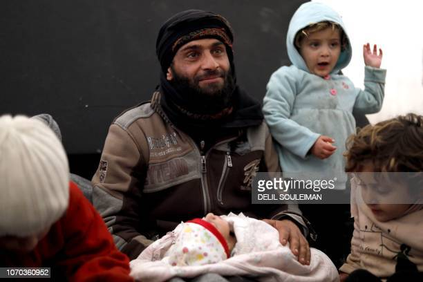 Abu Faraj a displaced Syrian from the locality of alShaafa holds his newborn in his arms inside a tent in the Internallly Displaced Persons camp of...