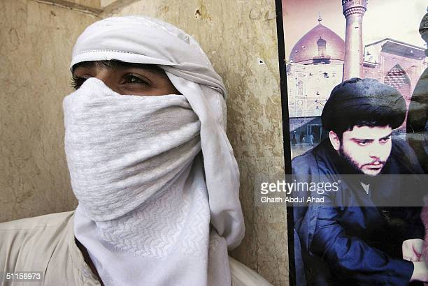 Abu Haqid a British volunteer stands outside the Imam Ali shrine by a poster of Iraqi Shiite Muslim radical cleric Moqtada alSadr on August 10 2004...