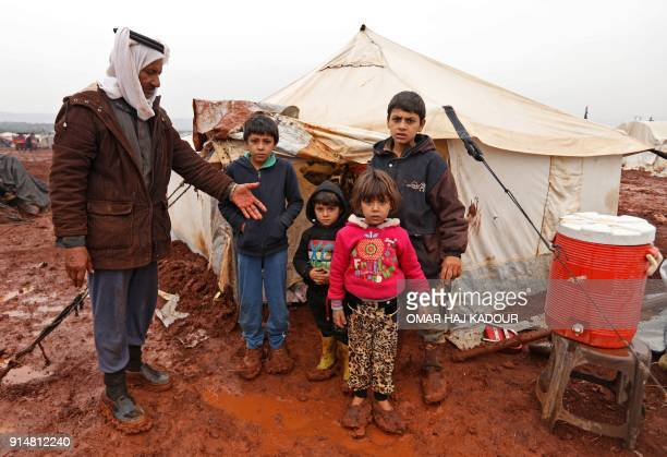 Abu Khaled stands next to his children at makeshift camp for internally displaced people in Batabu on the border between Syria's Idlib and Aleppo...