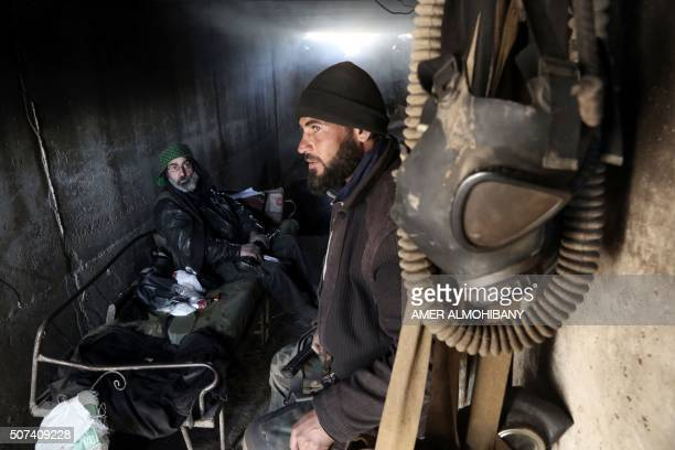 Abu Mahmud a 52yearold rebel fighter belonging to the Faylaq alRahman brigade speaks with a fellow fighter next to gas masks inside a tunnel used as...