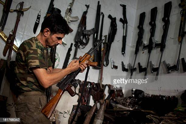 Abu Mohammad checks an AK47 at his gun shop in the Fardos district of Syria's northern city of Aleppo on September 21 2013 While most Syrians get...