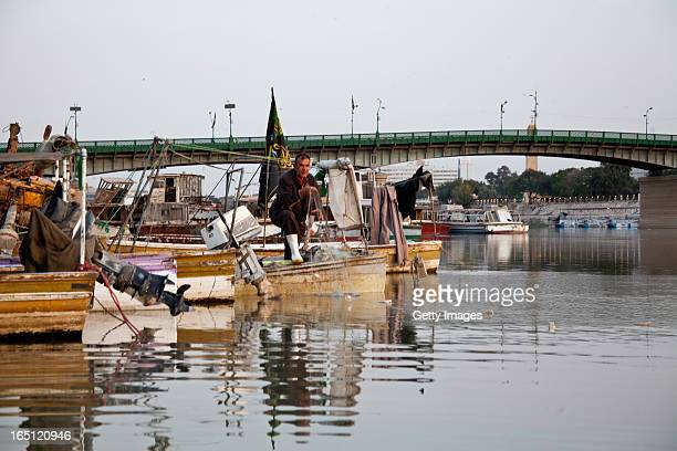 Abu Mustafa fishes from a boat on the Tigris river early in the morning on March 29 2013 in Baghdad Iraq Ten years after the regime of Saddam Hussein...