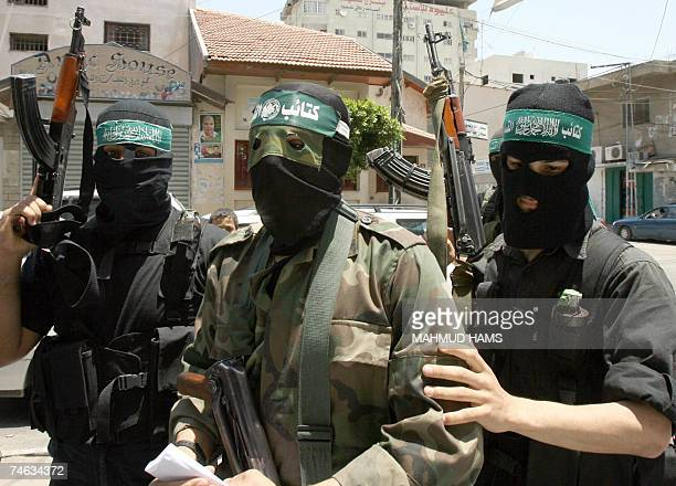 Abu Obeida a spokesman for Hamas's armed wing walks flanked by armed men to give a press conference in Gaza City 15 June 2007 Hamas seized full...