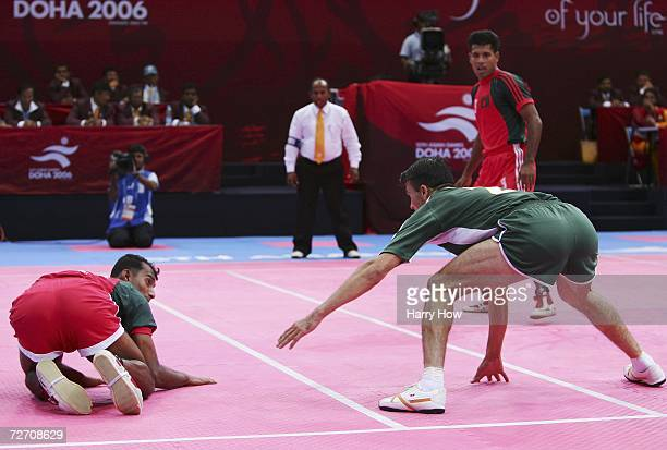 Abu Salah Musa of Bangladesh avoids the tackle by Nasir Ali of Pakistan during the Men's Kabaddi Round Robin Match Five between India and Bangladesh...