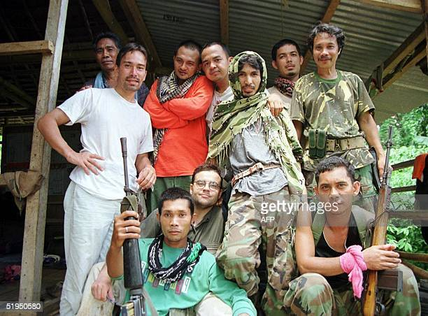 Abu Sayyaf fighters including Commander Global and Dr Abu pose with journalists Cyril Payen Philippe Abdelkafi and Frederick Alvarez pose in their...