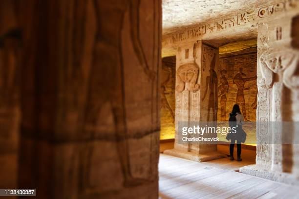 abu simbel - traveller inside nefertari temple in egypt - ancient civilization stock photos and pictures