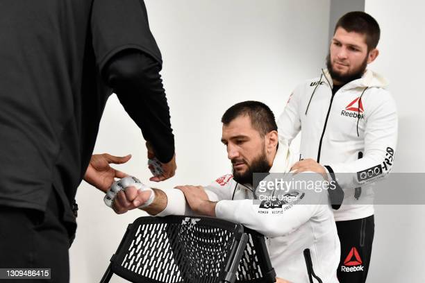 Abubakar Nurmagomedov of Russia has his hands wrapped prior to his fight as his cousin and former UFC lightweight champion Khabib Nurmagomedov looks...