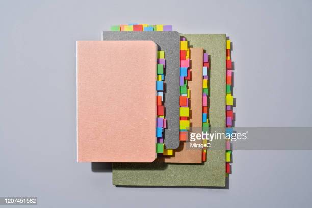 abundance of colorful bookmarks on note pads - 積み重ねる ストックフォトと画像