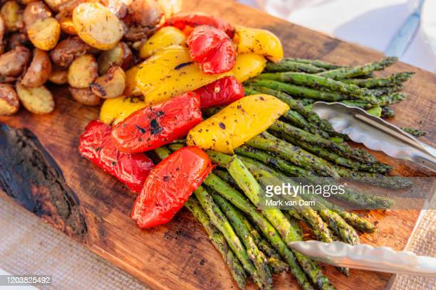 abundant platter of grilled and roasted asparagus, red and yellow peppers, and roasted potatoes - 盛り付け ストックフォトと画像