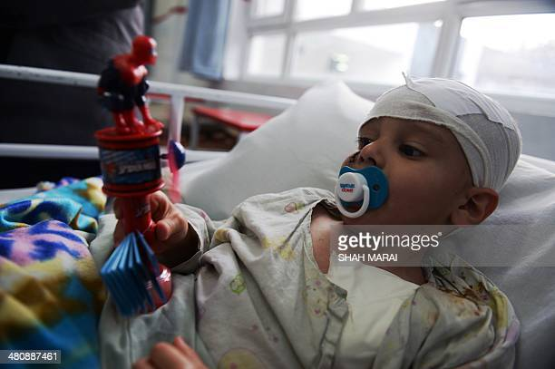 Abuzar Ahmad the youngest son of slain Afghan AFP reporter Sardar Ahmad plays with a spiderman toy at a local hospital in Kabul on March 27 2014 The...