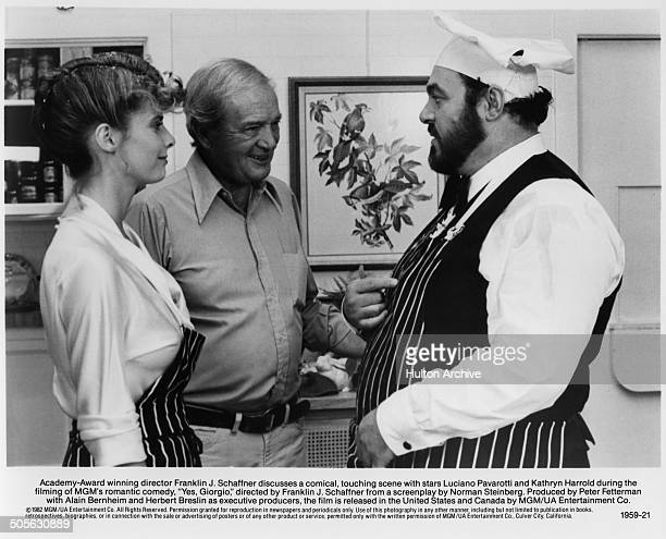 Academy Award Director Franklin J Schaffner talks with Kathryn Harrold and Luciano Pavarotti behind the scenes of the movie Yes Giorgio circa 1982