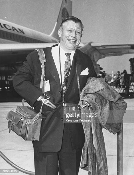 Academy Award winning actor Harold Russell smiling as he arrives at the airport carrying his luggage in the country to take part in the Assembly of...