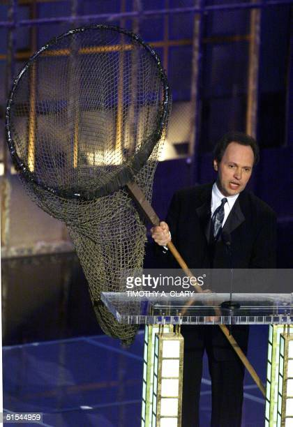 Academy Awards host Billy Crystal holds a net to catch Italian director Roberto Benigni who last year walked across the auditorium seats to receive...
