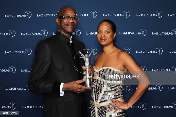 Academy Chairman Edwin Moses and wife Michelle pose with the trophy during the 2014 Laureus World Sports Awards at the Istana Budaya Theatre on March...