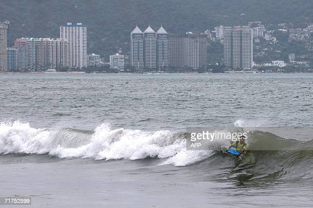 A teenager enjoys body boarding at a beach in Acapulco despite the alert warning issued by the Mexican authorities due to hurricane John 30 August...