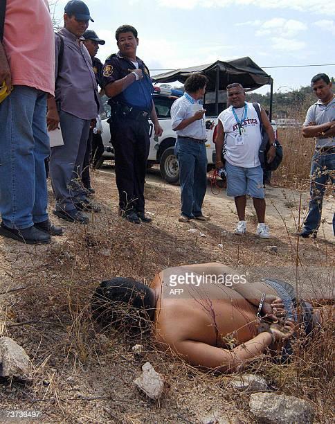 Un hombre que fue ejecutado de nueve balazos y abandonado con las manos esposadas es observado por la policia y periodistas en una calle del puerto...