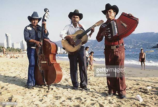 Drei Mexikaner mit Kontrabass Gitarre und Akkordeon spielen am Strand MariacchiMusik Undatiertes Foto
