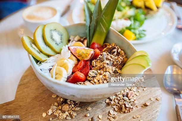 Acari bowl with fresh fruits, nuts and cereal in it