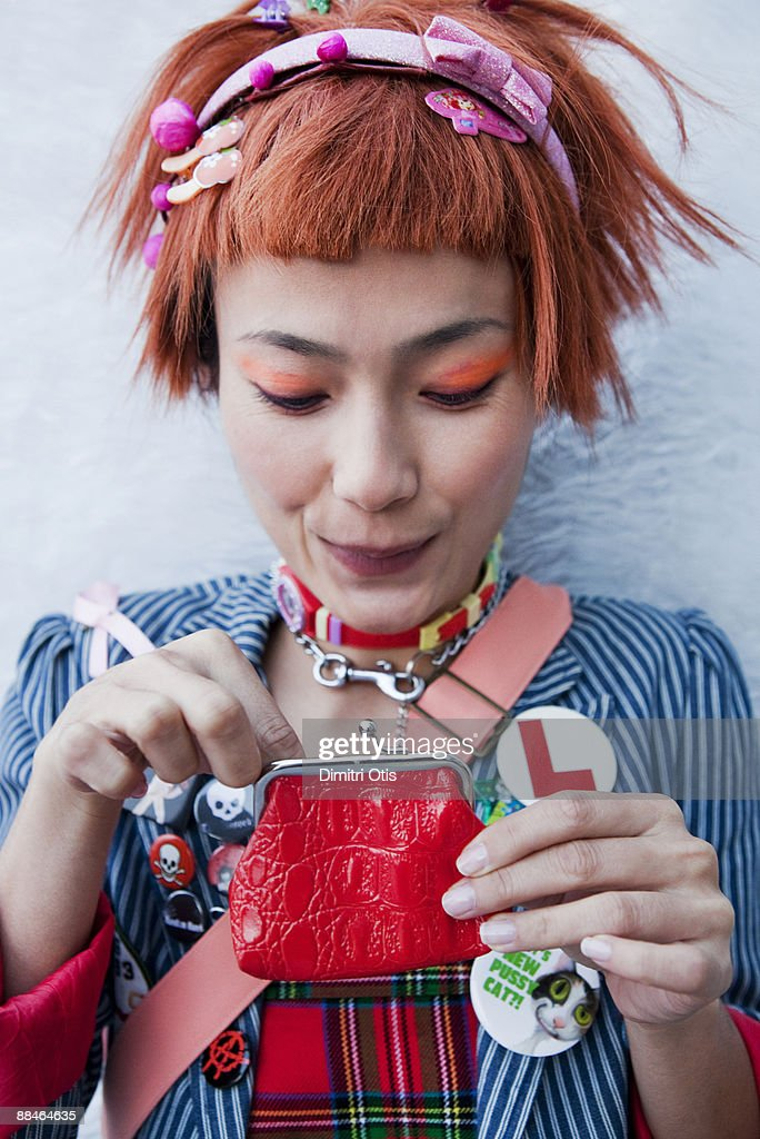 accessorized asian woman looking in her purse : Stock Photo