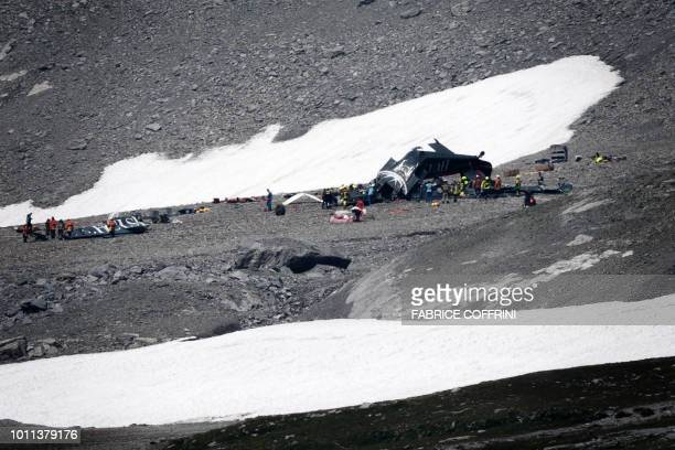 Accident investigators and rescue personnel gather around the wreckage of a Junkers JU52 aircraft at Flims on August 5 after the aeroplane crashed...