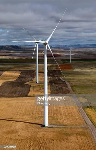 Acciona wind turbines operate above wheat fields at the NaturEner USA LLC Glacier wind energy farm in Ethridge Montana US on Monday Aug 30 2010...