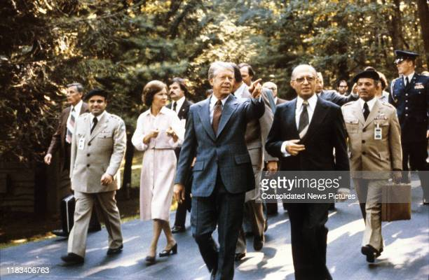 Accompanied by a large group of others, US President Jimmy Carter and Israeli Prime Minister Menachem Begin walk together during the Egyptian-Israeli...