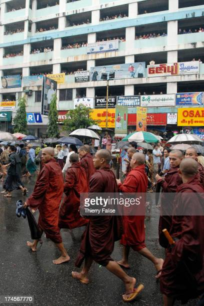 Accompanied by civilians and watched by a building's occupants Burmese Buddhist monks protesting against the military junta are marching in the...