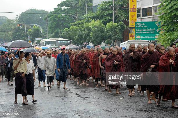 Accompanied by civilians Burmese Buddhist monks protesting against the military junta who are marching in the streets of Rangoon