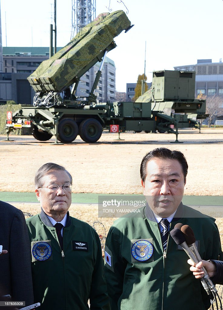 Accompanied by Defence Minister Satoshi Morimoto (L), Japanese Prime Minister Yoshihiko Noda (R) answers questions from reporters in front of a Patriot Advanced Capability-3 (PAC-3) missile launcher outside the Defence Ministry in Tokyo on December 7, 2012. Japan on December 7 issued the order to shoot down a North Korean rocket if it threatens the nation's territory, the top government official said. Tokyo has readied surface-to-air missiles in and around Tokyo, as well as in Okinawa, and is putting its armed forces on standby ahead of Pyongyang's planned missile launch. AFP PHOTO / Toru YAMANAKA