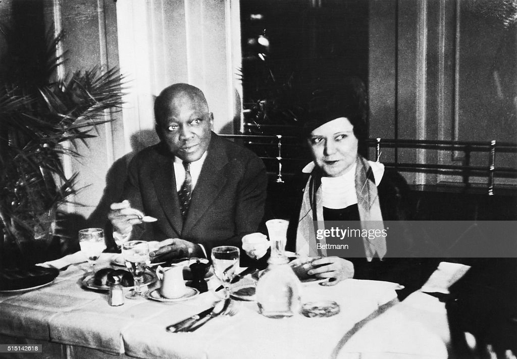 Accompanied by his beautiful white wife Irene, Jack Johnson, famous former world heavyweight boxing champion, enjoys luncheon in a restaurant on his arrival in Paris from Brussels, Belgium, where he engaged in a series of wrestling matches.