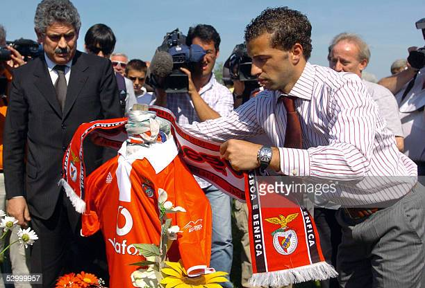 Accompanied by his chairman Luis Felipe Viera captain of champion football team Portuguese Benfica Simao Sabrosa puts a teamscarf on the grave of...