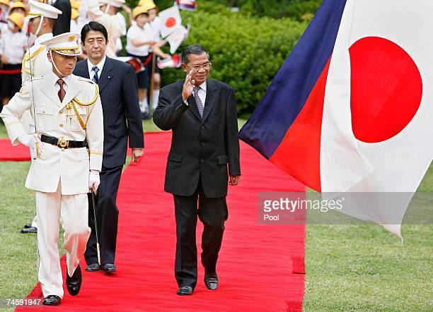 Accompanied by his Japanese counterpart Shinzo Abe Cambodian Prime Minister Hun Sen waves to Japanese honor guards during a welcoming ceremony at...