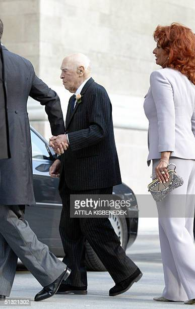 Accompanied by his wife Italian film star Sophia Loren and holding his son Eduard Ponti's hand Italian producer Carlo Ponti arrives at the Basilica...