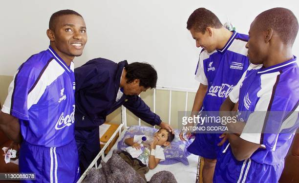 Accompanied by members of the Honduran soccer team, Honduran head coach Ramon greets a hospitalized child, 25 July 2001, during a visit to a Red...