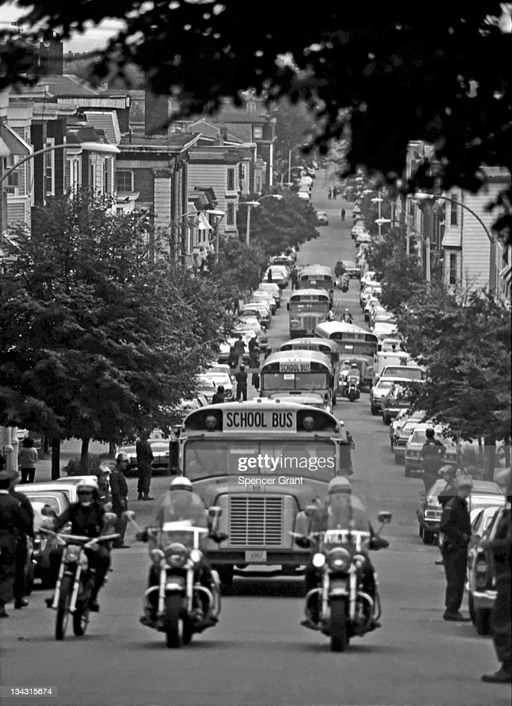 Accompanied by motorcycle-mounted police, school buses carrying African American students arrive at formerly all-white South Boston High School on September 12, 1974, the first day of federal court-ordered busing to achieve racial balance in the city's de facto segregated schools.