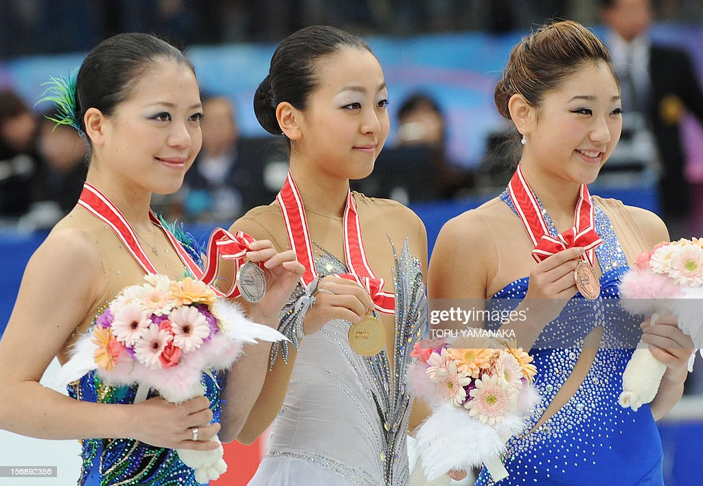 Accompanied by second place Akiko Suzuki (C) of Japan and third placed Mirai Nagasu (R) of the US, Mao Asada (C) of Japan poses for photographers during the awarding ceremony for the women's event in the NHK Trophy, the last leg of the six-stage ISU figure skating Grand Prix series, in Rifu, northern Japan, on November 24, 2012. AFP PHOTO/Toru YAMANAKA