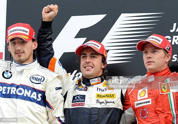 Accompanied by second-placed Robert Kubica of Poland and third-placed Kimi Raikkonen of Finland, Spain's Fernando Alonso of Renault raises his fist...